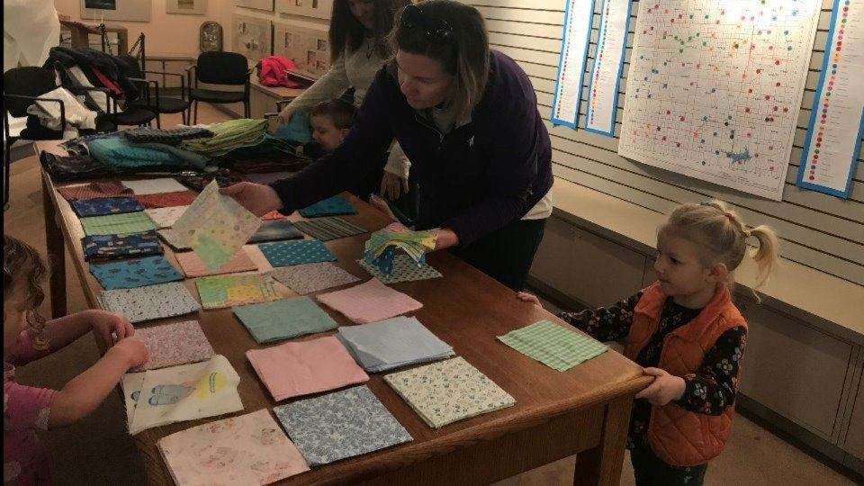 Little girl picking out quilt blocks